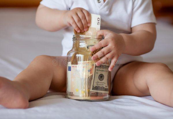 childrens-hands-money-glass-jar-close-up-69458594